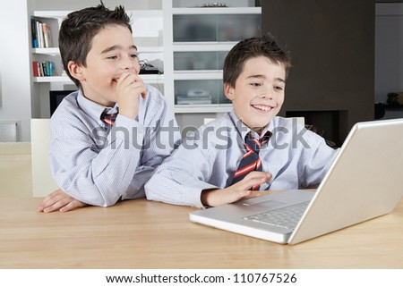 Two identical twin brothers sharing a laptop computer to do their homework on a wooden table at home.