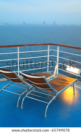 Two illuminated  deck-chair on ship deck overlooking city shoreline at evening - stock photo