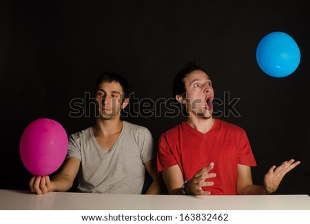Two immature guys fooling around with balloons - stock photo