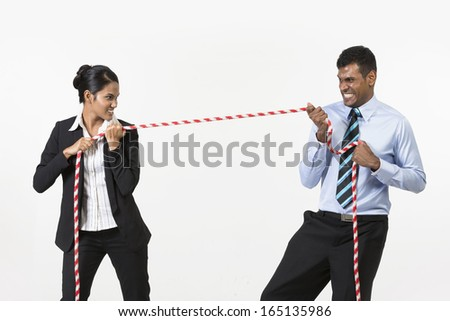 Two Indian business people playing tug war. Isolated on white background - stock photo