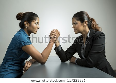Two Indian business women having an arm wrestle challenge. Conceptual business image about power and control. - stock photo