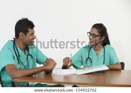 Two Indian doctors sitting working at a desk together - stock photo