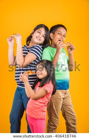 two indian girls and one boy eating pizza over yellow background - stock photo