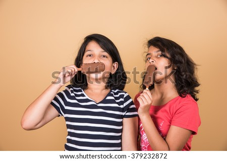 two indian girls eating ice cream or ice candy, two asian girl and ice cream or ice candy, isolated on brown background, ten year old indian girls enjoying ice cream or ice candy or choko bar - stock photo