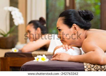 Two Indonesian Asian women in wellness beauty spa having aroma therapy massage with essential oil, looking relaxed - stock photo