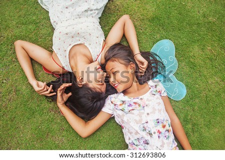 two indonesian sisters lying down on a grass - stock photo