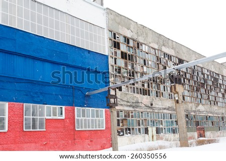 Two industrial buildings old and new. Old with broken windows. New painted in white, blue and red. - stock photo