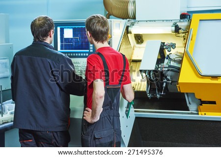two industrial workers at cnc turning machine center in tool manufacture workshop - stock photo