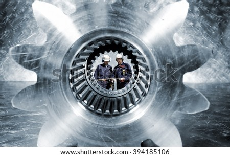two industry workers seen through a giant cogwheels axle, slight blue toning - stock photo