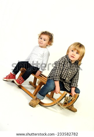 two infant kids seating on the vintage wooden sledge isolated on White background