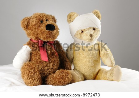 two injured teddy bears holding each other - stock photo