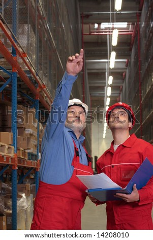two inspectors in uniforms and hardhats in warehouse - stock photo