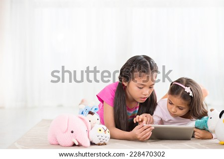 Two interested little girls using tablet computer  - stock photo