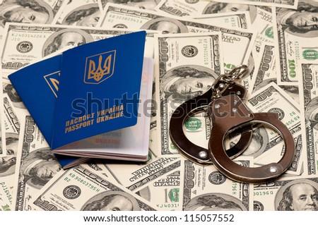 Two international Ukrainian passport with handcuffs on US dollars background - stock photo