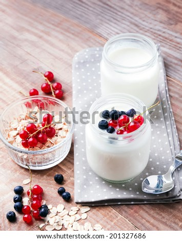 Two jars of fresh yogurt, berries  and oatmeals on the wooden table