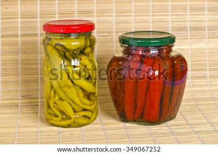 Two jars with marinated peppers on bamboo material background - stock photo