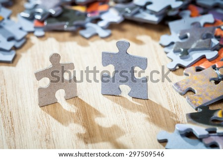 Two jigsaw puzzle pieces dropping shadows on a table. Shallow depth of field