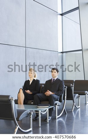 Two job candidates sitting in a waiting room - stock photo