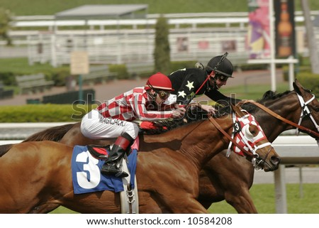 Two jockeys struggle for the lead in a thoroughbred horse race. - stock photo