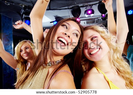 Two joyful girls dancing in night club and having fun - stock photo