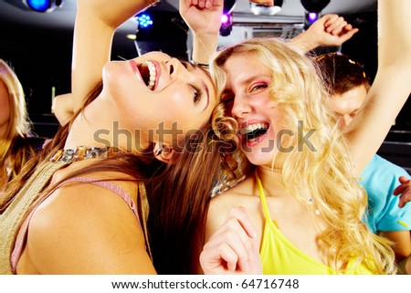 Two joyful girls laughing in night club at disco - stock photo
