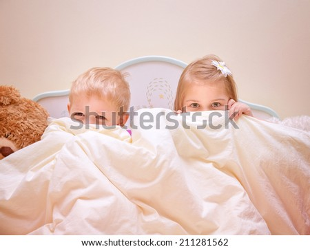 Two joyful kids playing game in bedroom, siblings sitting on the bed and covered with blanket, hide and seek, happy childhood concept - stock photo