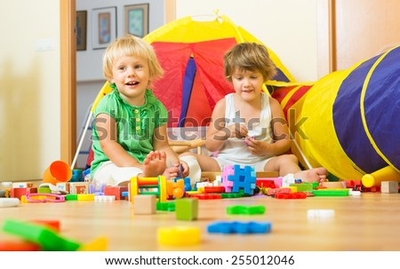 Two joyful little sisters playing with toys together at home  - stock photo