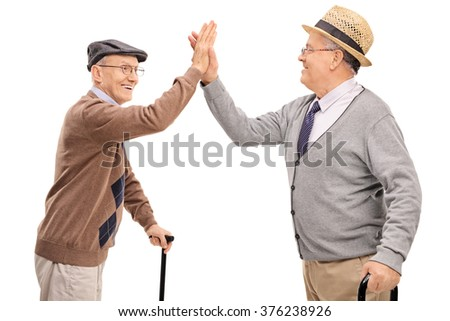 Two joyful senior gentlemen high-five each other isolated on white background