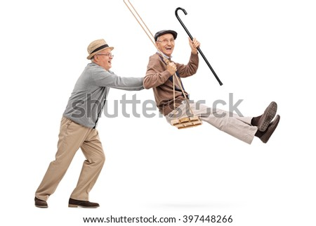 Two joyful senior gentlemen swinging on a swing and having fun isolated on white background - stock photo