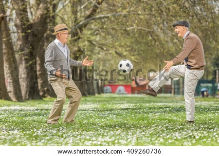 Two joyful seniors playing football in a park on a beautiful spring day - stock photo