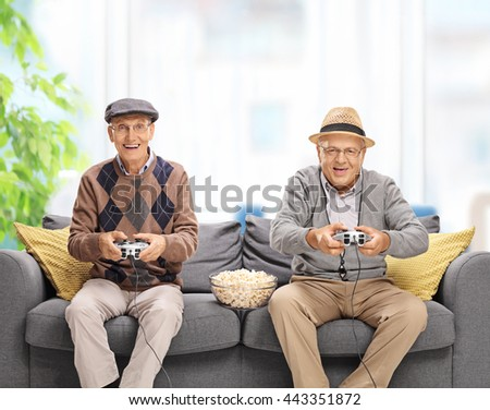 Two joyful seniors playing video games seated on a gray sofa at home