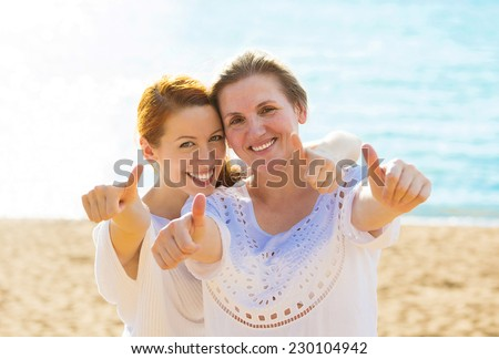 Two joyful women mother daughter showing thumbs up having fun vacation on beach. Positive human emotion face expression feeling life perception peace of mind concept. Free happy people enjoying nature - stock photo