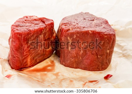Two juicy Prime Cut Filet Mignon being unwrapped from butcher paper against white background with copy space.