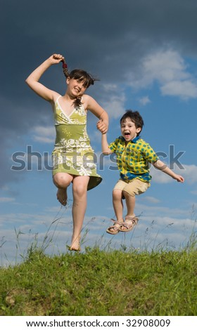 Two jumping children - little brother and big sister - stock photo