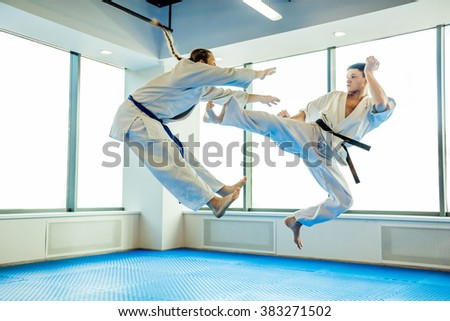 Two karate fighters showing technical skill while practicing Martial arts in a fight club - stock photo