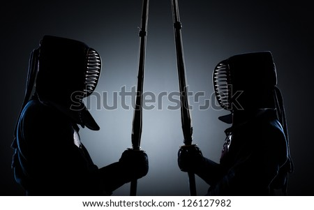 Two kendo fighters opposite each other with shinai. Japanese martial art of sword fighting - stock photo
