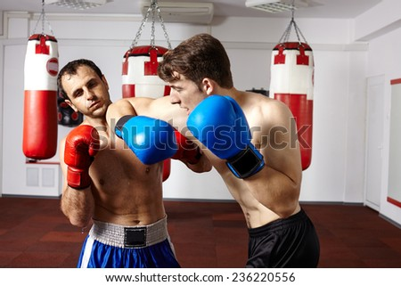 Two kickbox or muay thai fighters sparring in the gym - stock photo
