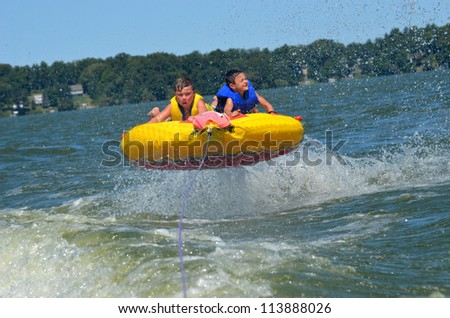two kids airborne while tubing on a lake