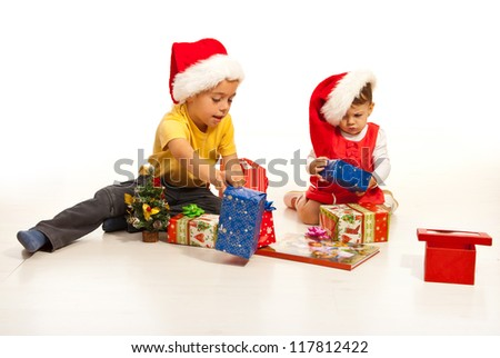 Two kids arrange  Christmas gifts and sitting together on floor - stock photo