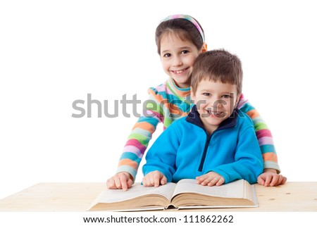 Two kids at the table reading the book together, isolated on white - stock photo