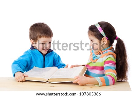 Two kids at the table sharing the book, isolated on white - stock photo