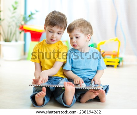 Two kids boys sitting beside him and read a book - stock photo