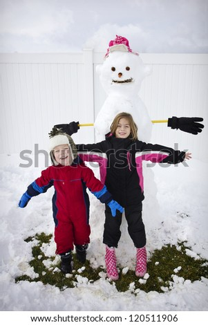 Two Kids building a snowman - stock photo