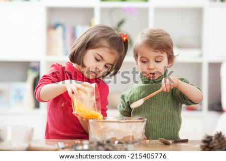 Two kids cooking at home. - stock photo