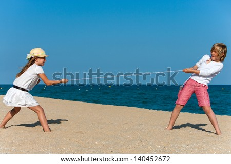 Two kids having a tug war on the beach.