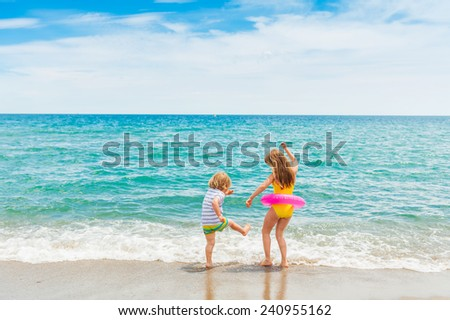 Two kids having fun on summer vacation, playing in the sea - stock photo