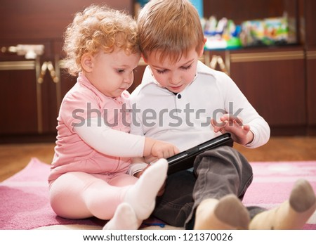 Two kids having fun with a digital tablet - stock photo