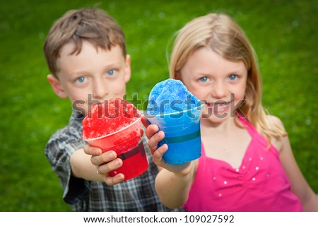 Two kids hold snow cones out to the camera. - stock photo