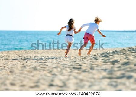 Two kids holding hands running away on sandy beach. - stock photo
