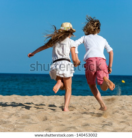 Two kids holding hands running towards sea. - stock photo